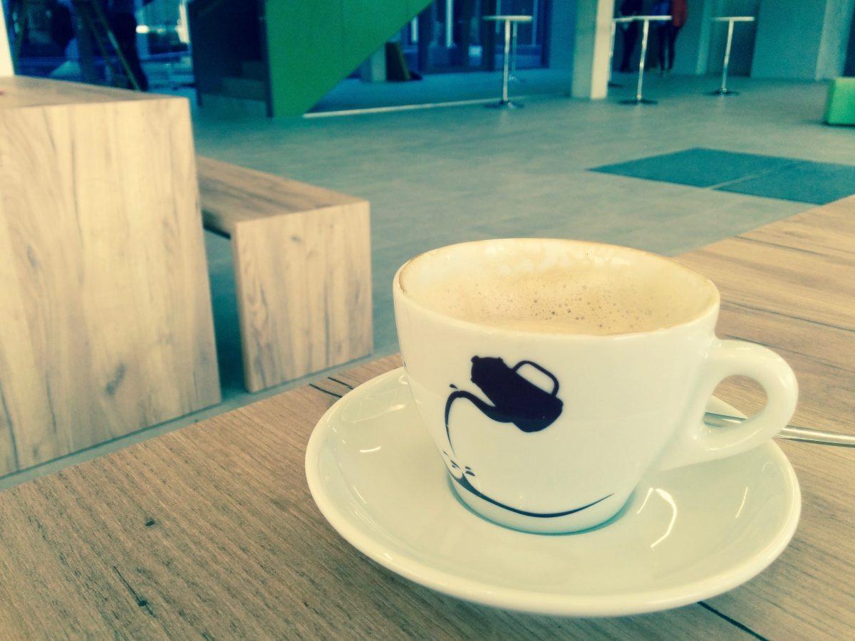 Eine Tasse Cappuccino, leicht angetrunken, auf Tisch im Eingangsbereich der TechBase Regensburg