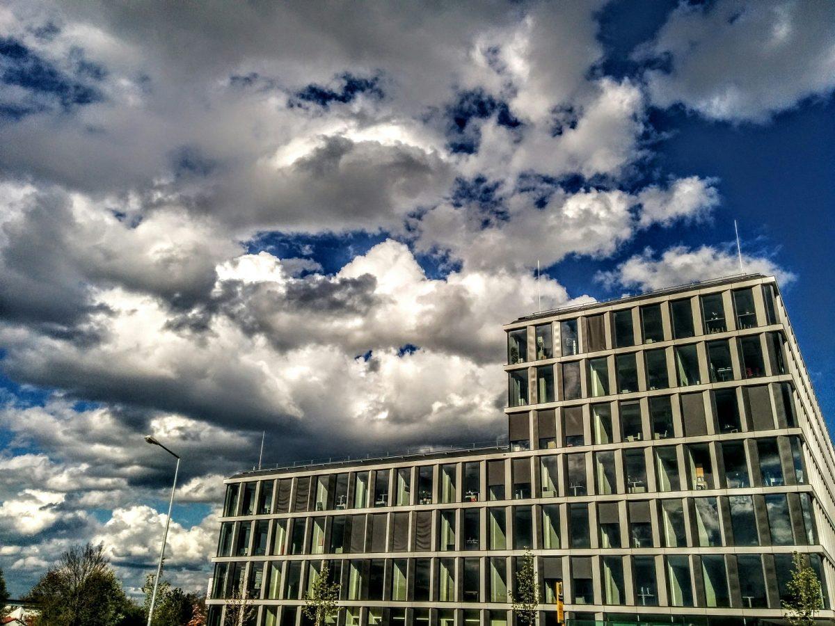 Blick auf das die TechBase Regensburg das Innovationszentrum von der Bushaltestelle gegenüber. Man sieht viele Wolken, denn der April macht was er will.