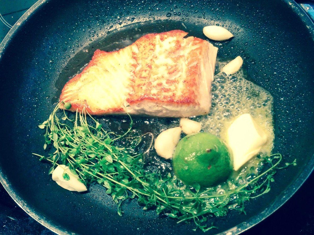Foto von einer Pfanne mit Lachs, Zitrone, Thymian, Knoblauch. Öl und Butter