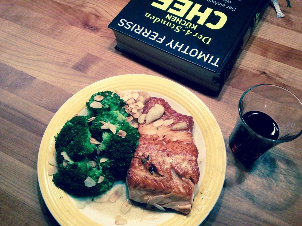 Foto von Lachs, Broccoli, Mandeln, Rotwein und einem Buch